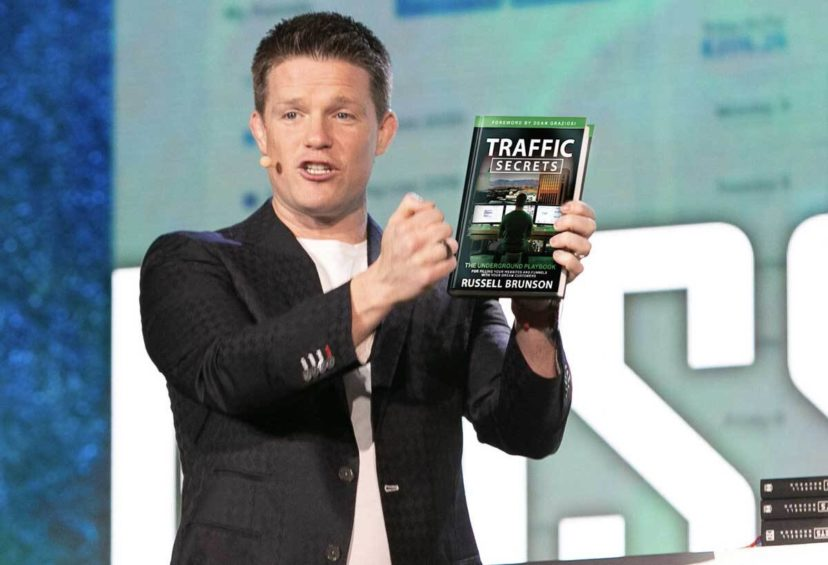 Russell Brunson holds a copy of his book Traffic Secrets